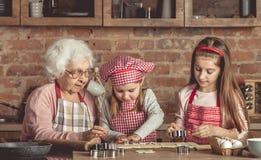 Pequeña abuelita de la ayuda de las nietas para cocer las galletas Fotos de archivo libres de regalías