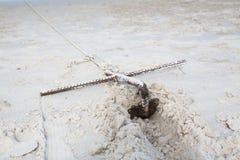 Pequeña ancla tradicional oxidada en una playa por el mar fotografía de archivo