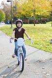 Pequeña bici biracial asiática del montar a caballo de la muchacha en parque Foto de archivo libre de regalías