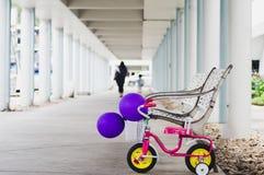 Pequeña bici con los globos hermosos del color Y detrás del wa largo fotografía de archivo
