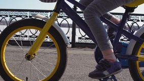 Pequeña bici rubia de cinco años del montar a caballo de la muchacha en un parque viejo almacen de video