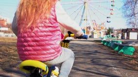 Pequeña bici rubia de cinco años del montar a caballo de la muchacha en un parque viejo metrajes