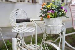 Pequeña bicicleta de adornamiento blanca con el ramo de la flor Fotografía de archivo