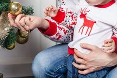 Pequeña bola de la decoración del Año Nuevo del control del niño en manos Fotos de archivo