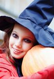 Pequeña bruja con una calabaza Foto de archivo