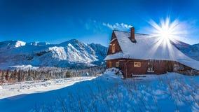 Pequeña cabaña de la montaña en un amanecer del invierno Imagen de archivo