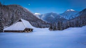 Pequeña cabaña de la montaña en valle del invierno en la puesta del sol Foto de archivo libre de regalías