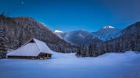 Pequeña cabaña de la montaña en valle del invierno en la puesta del sol Fotografía de archivo