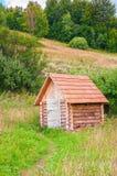 Pequeña cabaña de madera de madera en prado del bosque de la montaña Foto de archivo libre de regalías