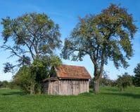 Pequeña cabaña de madera debajo de árboles frutales Fotos de archivo libres de regalías
