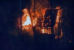 pequeña cabaña de madera en el fuego en la noche Imagenes de archivo