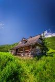 Pequeña cabaña en un valle de la montaña en el amanecer Imagen de archivo