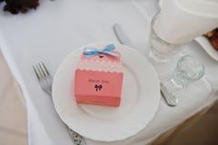Pequeña caja con los caramelos en el plato en la tabla de la boda de huéspedes con s imagenes de archivo