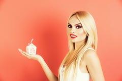 Pequeña caja de regalo blanca del control rubio atractivo joven de la mujer foto de archivo libre de regalías