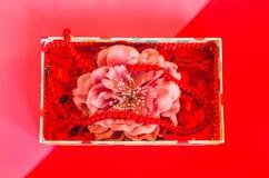 Pequeña caja de regalo con la flor, los pequeños corazones y las gotas en fondo rosado fotografía de archivo