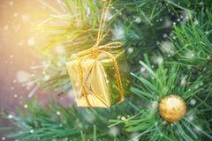 Pequeña caja de regalo del oro en el árbol de navidad con caer de la nieve Foto de archivo libre de regalías