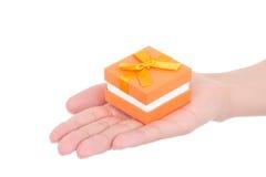 Pequeña caja de regalo en la mano de la mujer aislada en el fondo blanco Fotos de archivo