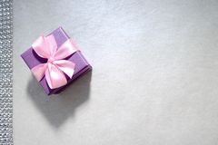 Pequeña caja de regalo de la cartulina festiva hermosa violeta del regalo con un arco en un fondo gris claro imagen de archivo libre de regalías