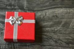 Pequeña caja de regalo roja en la tabla de mármol Fotos de archivo