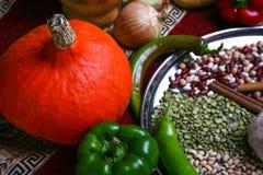 Pequeña calabaza amarilla y pimienta verde, cebolla, guisantes verdes, legumbres de Halloween en la placa Visión superior, cierre Imágenes de archivo libres de regalías