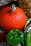 Pequeña calabaza amarilla y pimienta verde, visión superior, cierre de Halloween para arriba Fotos de archivo libres de regalías