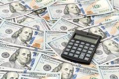 Pequeña calculadora en cientos billetes de dólar Fotografía de archivo libre de regalías
