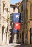 Pequeña calle en el centro de Narni con las banderas rojas y azules fotografía de archivo