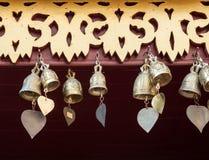 Pequeña campana de cobre amarillo con la cola de la forma del corazón Imagenes de archivo
