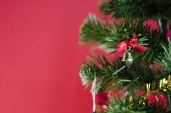 Pequeña campana en el árbol de navidad en fondo rojo Fotos de archivo libres de regalías