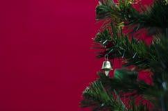 Pequeña campana en el árbol de navidad en fondo rojo Foto de archivo