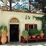 Pequeña capilla griega hermosa con las macetas (Creta, Grecia) Imagen de archivo libre de regalías