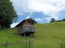 Pequeña casa alpina de madera del estilo en la colina Imágenes de archivo libres de regalías