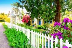 Pequeña casa amarilla exterior con la valla de estacas blanca Imagenes de archivo