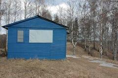 Pequeña casa azul en hierba seca Imagen de archivo libre de regalías