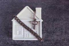 Pequeña casa blanca, cadena y una llave decorativa en un backgrou oscuro Fotografía de archivo