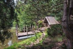 Pequeña casa de la madera con una balsa en la orilla Fotos de archivo libres de regalías