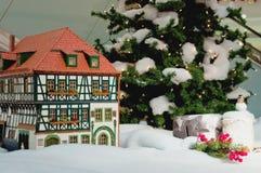 Pequeña casa de la Navidad cerca del árbol de navidad con las decoraciones imagen de archivo libre de regalías