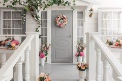 Pequeña casa de madera blanca con la puerta gris Decoración de la flor de la primavera Imágenes de archivo libres de regalías
