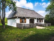 Pequeña casa de madera blanca en el campo imagen de archivo