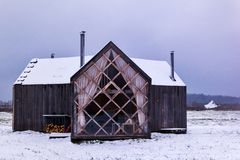 Pequeña casa de madera en el campo de nieve fotos de archivo