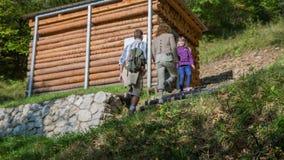 Pequeña casa de madera en el medio de la trayectoria en la montaña