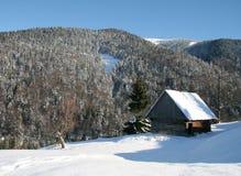Pequeña casa de madera en montañas del invierno Foto de archivo libre de regalías