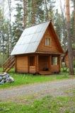 Pequeña casa de madera en una madera Fotos de archivo