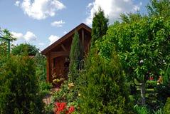 Pequeña casa de madera y el jardín Imagenes de archivo
