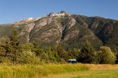 Pequeña casa debajo de la montaña en prado de oro Fotos de archivo libres de regalías