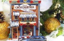Pequeña casa del juguete en el fondo del árbol de navidad foto de archivo