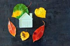 Pequeña casa del juguete entre las hojas de otoño coloridas foto de archivo libre de regalías