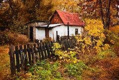 Pequeña casa en el bosque del otoño en la aldea Imagenes de archivo