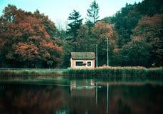 Pequeña casa en la costa del lago Imagen de archivo libre de regalías