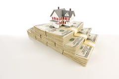 Pequeña casa en las pilas de cientos cuentas de dólar Foto de archivo libre de regalías